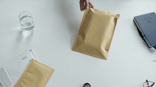 woman using packing bubble envelope brown