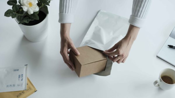 woman packing a box in a white mailing bag