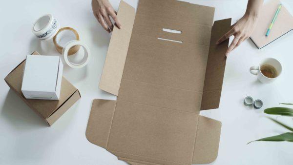 woman using self folding brown ecommerce mailing box