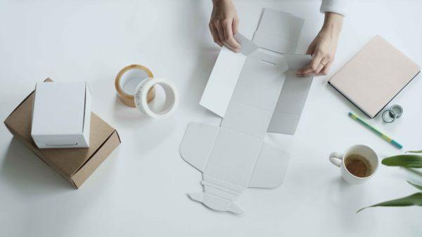 woman using self folding white ecommerce mailing box