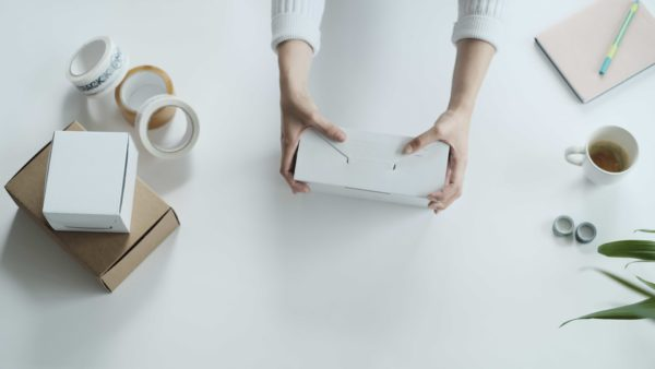 woman usingself folding white ecommerce mailing box